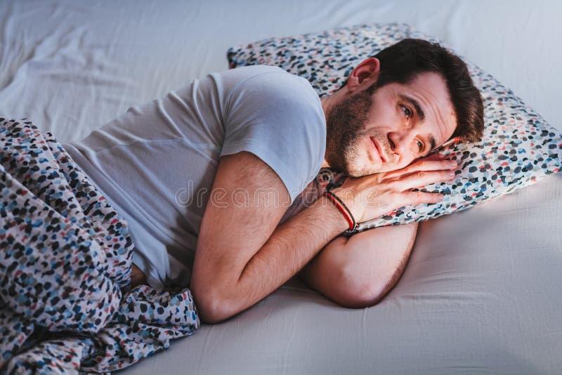 Ung man som vaknar upp i säng i morgonen royaltyfri fotografi