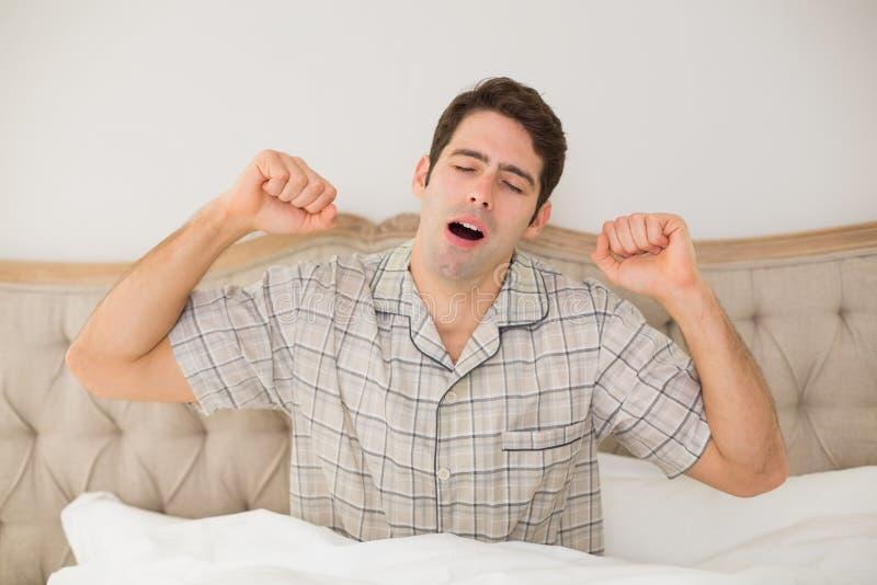 Ung man som vaknar upp i säng och sträcker hans armar arkivfoton
