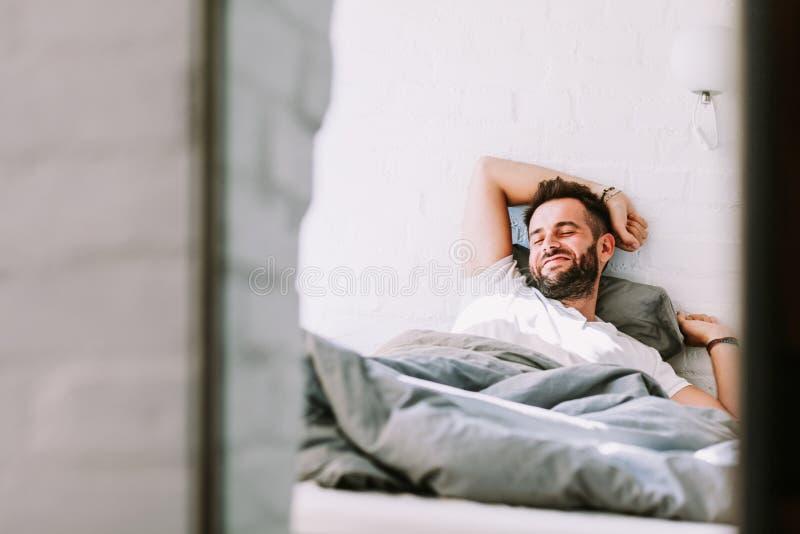 Ung man som vaknar upp i sängen royaltyfri fotografi