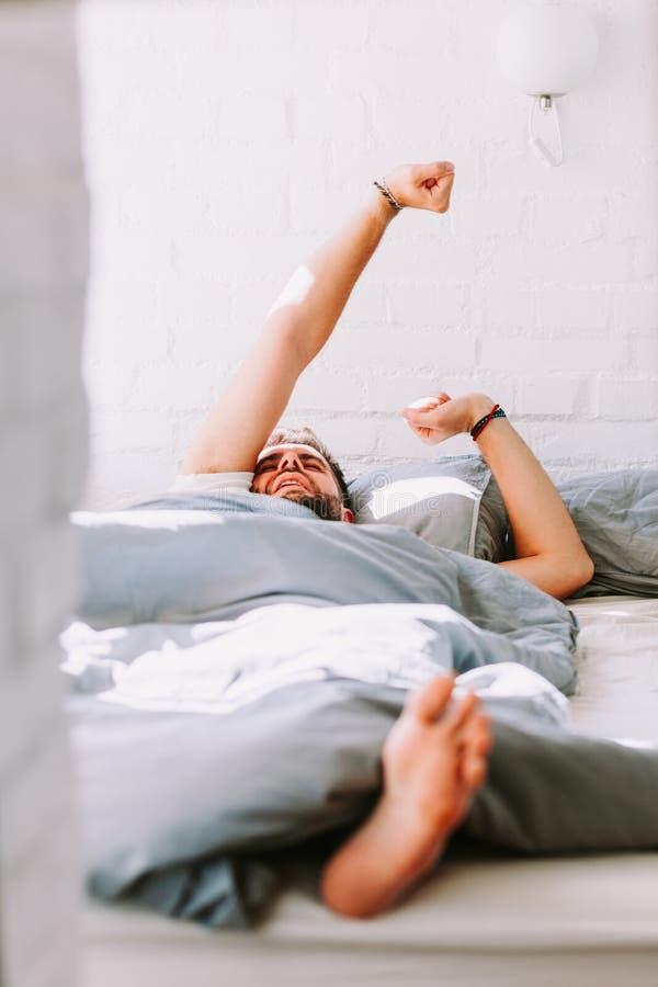 Ung man som vaknar upp i sängen royaltyfria foton