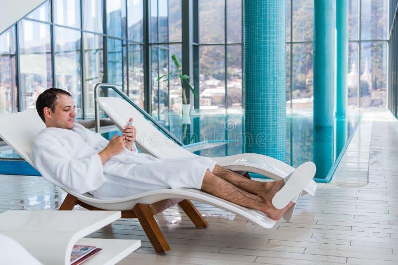 Ung man som vilar på soldagdrivare av simbassängen och använder mobiltelefonen royaltyfria foton