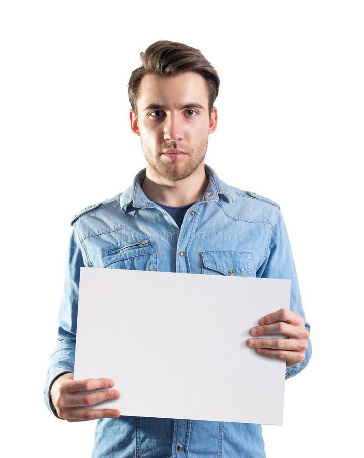 Ung man som visar en sida för tomt papper arkivfoto