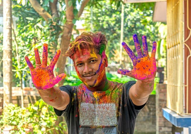 Ung man som visar färgrika målade händer under den Holi festivalen i Indien royaltyfri fotografi
