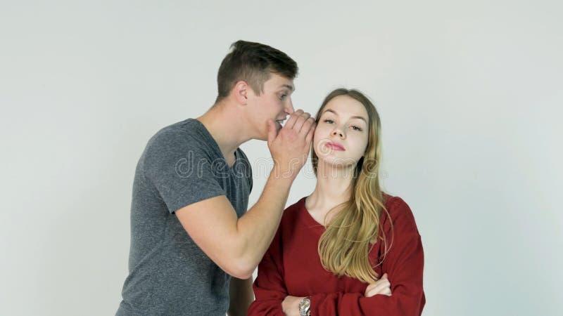 Ung man som viskar en hemlighet till en förvånad ung kvinna Den unga mannen berättar en hemlighet till flickan arkivfoto