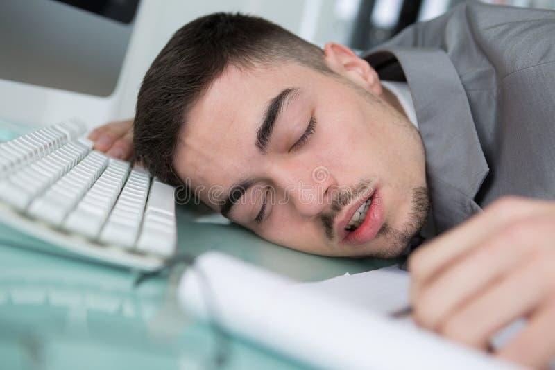 Ung man sovande bredvid datoren royaltyfri foto