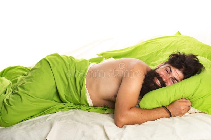 Ung man sover i sängen med kuddar hemma. stilig man f?r underlag. sleeper. S?mnig vak upp royaltyfri foto