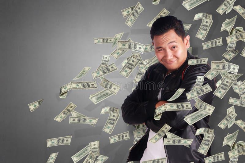 Ung man under regn av pengar royaltyfria bilder