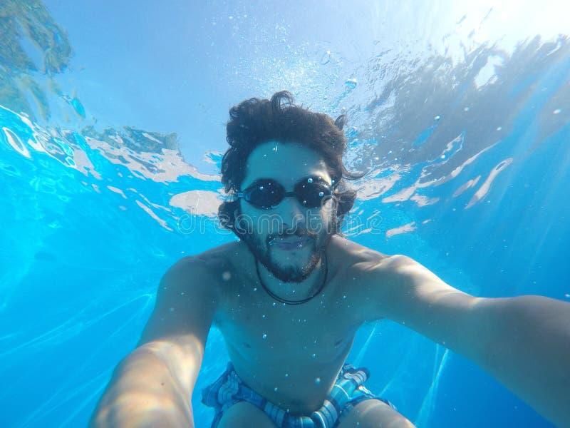 Ung man under vattnet av en simbassäng arkivfoto