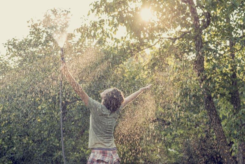 Ung man utanför i den gröna sommarnaturen som rymmer spr för trädgårds- slang royaltyfri foto