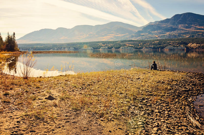 Ung man vid bergsjön royaltyfria foton
