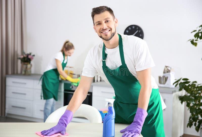 Ung manlig arbetare av lokalvårdservice som arbetar i kök royaltyfri fotografi