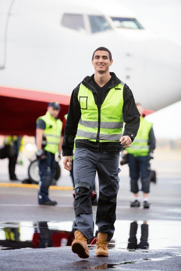 Ung manlig arbetare som går på våt landningsbana på flygplatsen royaltyfri fotografi
