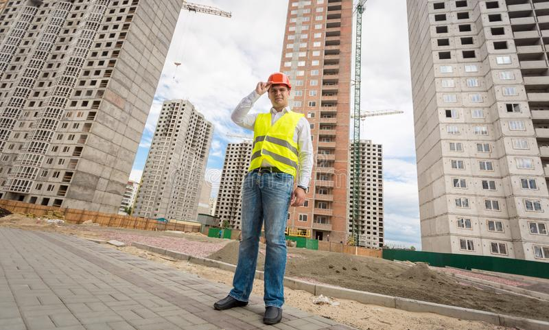 Ung manlig arkitekt i hjälmen som poserar mot nybyggen under konstruktion royaltyfri fotografi