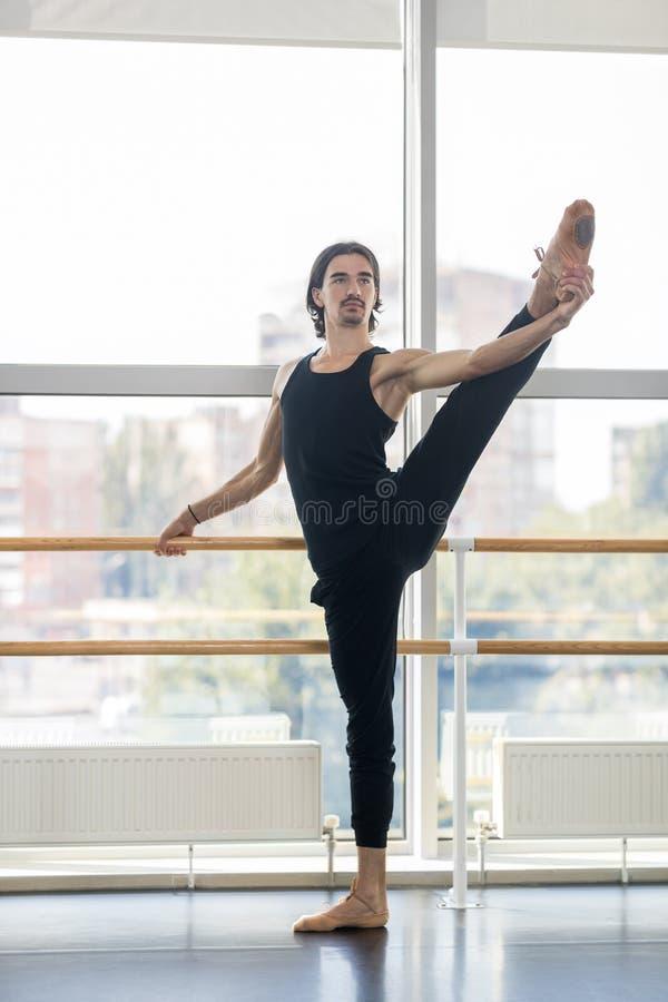 Ung manlig balettdansör Posing Near Barre, praktiserande elasticitet för latinamerikansk man fotografering för bildbyråer