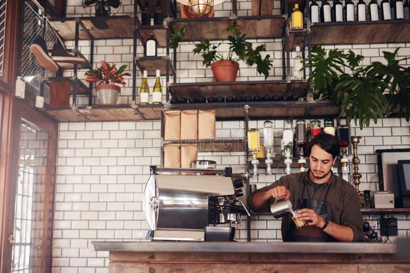 Ung manlig barista som gör en kopp kaffe royaltyfri bild