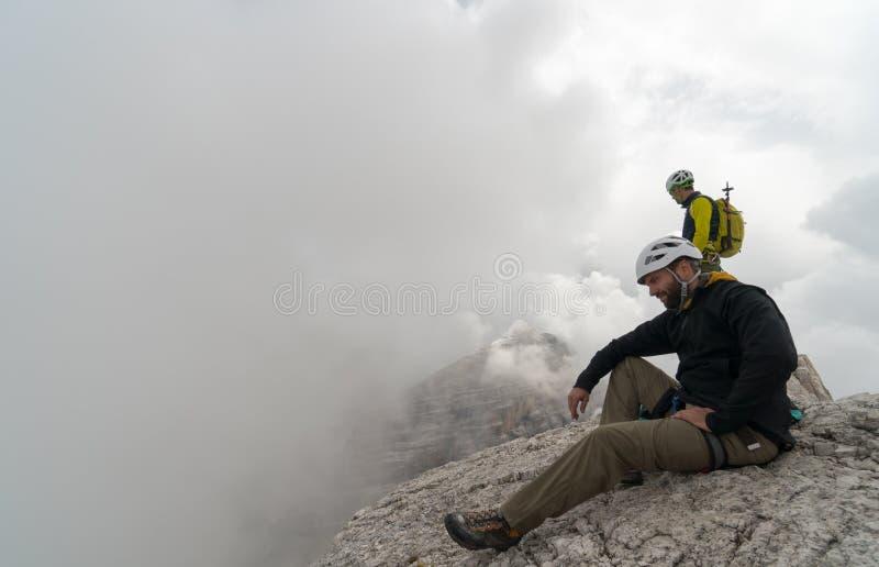 Ung manlig bergsbestigare på ett Dolomitebergmaximum som tycker om sikten med hans handbokanseende bakom arkivbilder