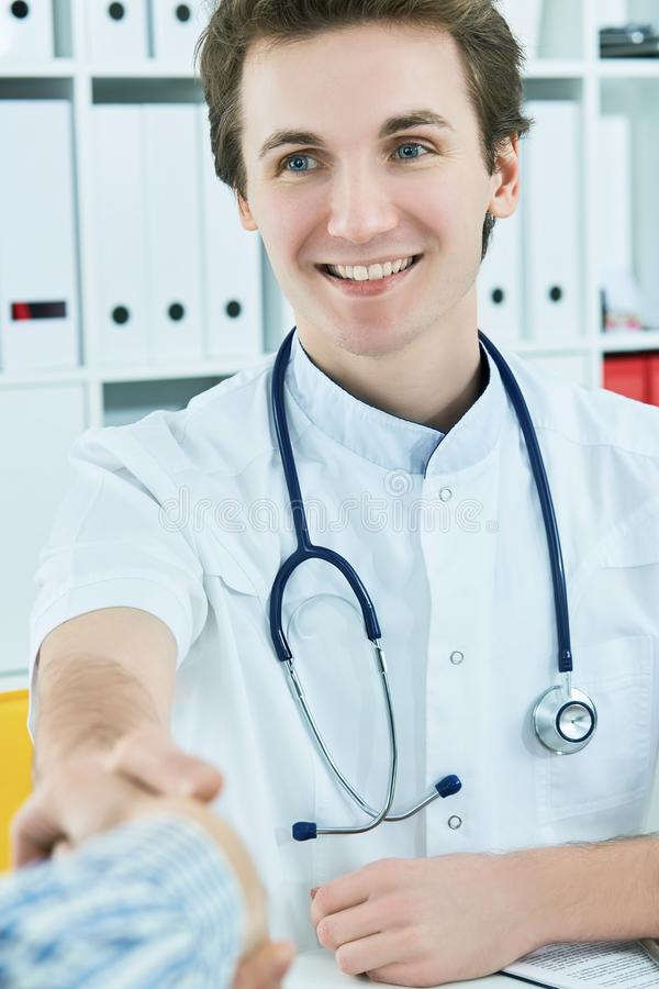 Ung manlig Caucasian doktor som skakar händer med patienten på det ljusa moderna kontoret för doktorer i sjukhus arkivfoto