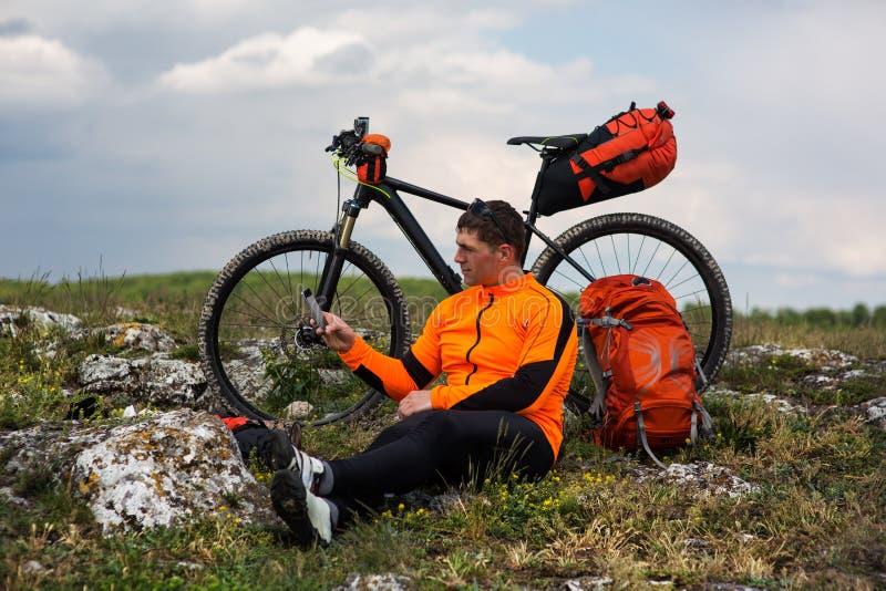 Ung manlig cyklist som talar på mobiltelefonen arkivbilder