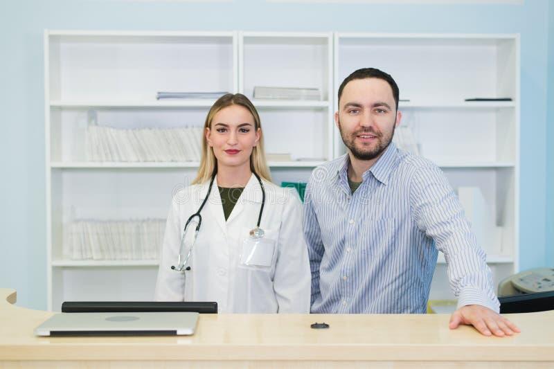 Ung manlig doktor med kollegan på doktors kontor doktor arbete Basa royaltyfri fotografi