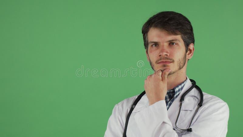 Ung manlig doktor som bort hänsynsfullt ser royaltyfri foto