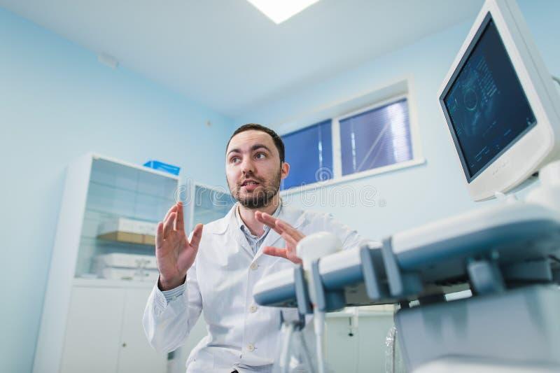Ung manlig doktor som förklarar ultraljudsundersökning till gravida kvinnan i sjukhus arkivfoto
