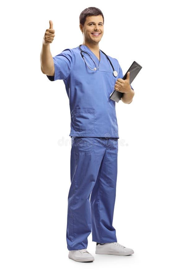 Ung manlig doktor som rymmer en skrivplatta och visar upp tummar royaltyfri foto