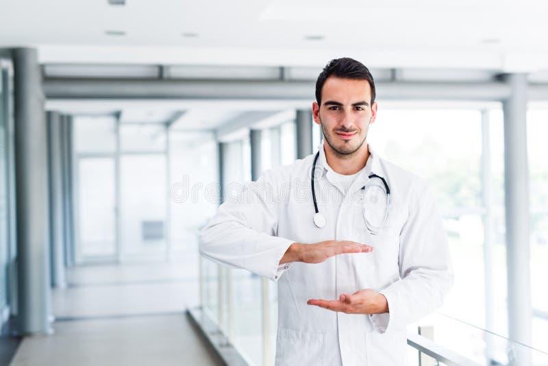 Ung manlig doktor som rymmer tomma händer royaltyfria foton