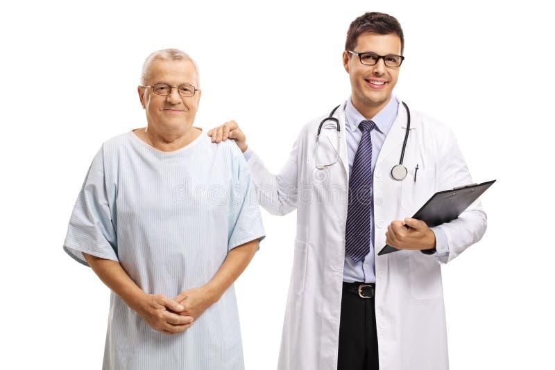 Ung manlig doktor som står med en äldre manlig patient och ser kameran royaltyfri fotografi
