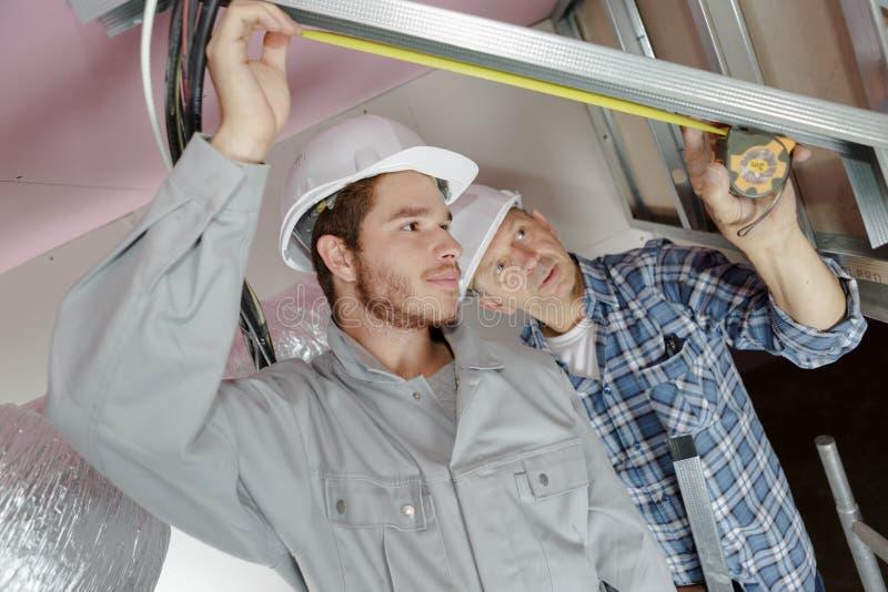 Ung manlig elektriker med mentorn royaltyfri fotografi