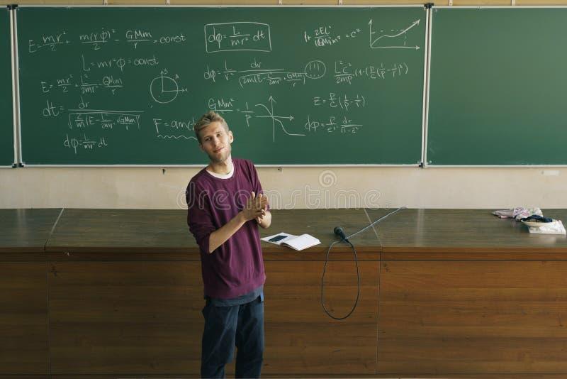 Ung manlig föreläsare i hörsalapplåden med svart tavla i bakgrunden arkivfoto