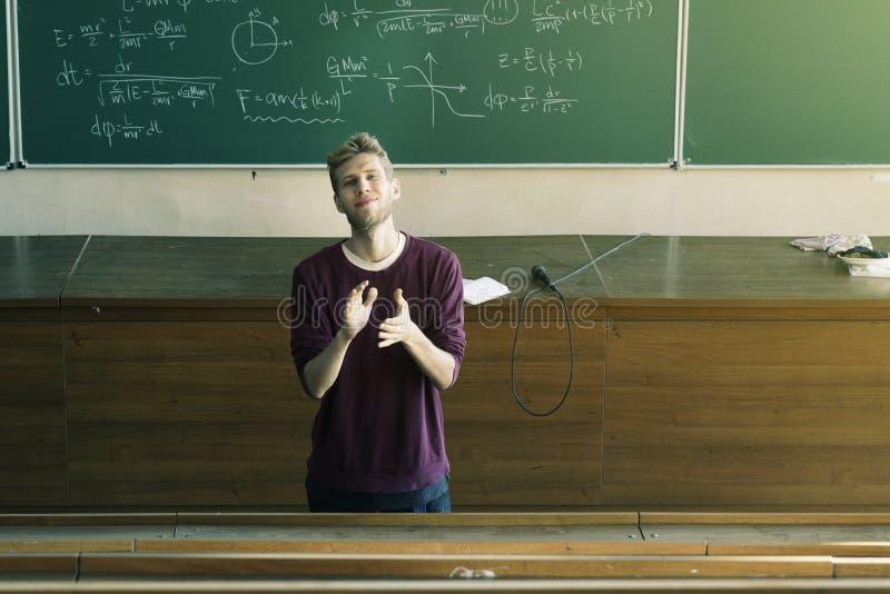 Ung manlig föreläsare i hörsalapplåden med svart tavla i bakgrunden arkivfoton