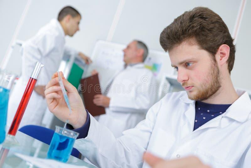Ung manlig forskare med vätskeprövkopian arkivfoton