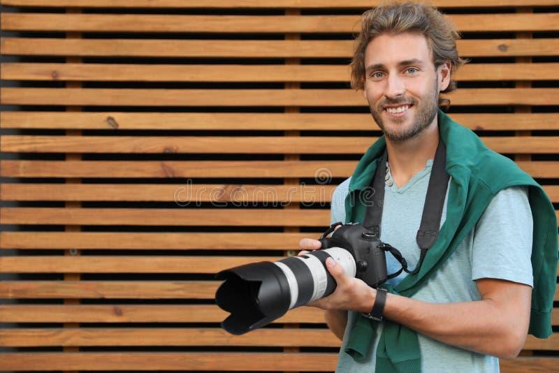 Ung manlig fotograf med den yrkesmässiga kameran nära träväggen royaltyfri foto