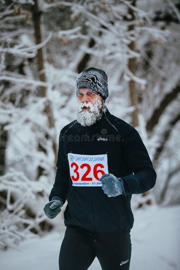 Ung manlig joggerspring till och med ett snöig parkerar gränden framsida och skägg i frost arkivfoto