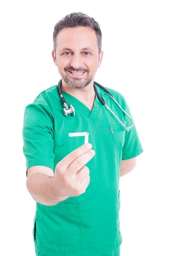 Ung manlig läkare som rymmer en bruten cigarett fotografering för bildbyråer