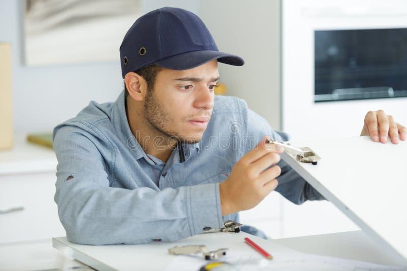 Ung manlig leverantör som monterar inpassat kök arkivfoto