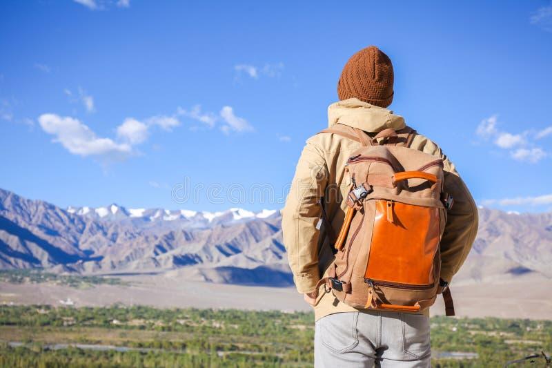 Ung manlig loppfotvandrare på beslutsamma hållande ögonen på berg för affärsföretag som ska klättras och fotvandras royaltyfria foton
