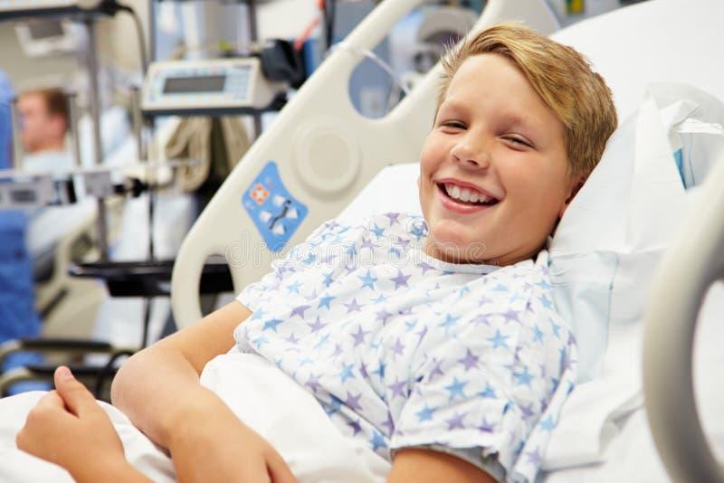 Ung manlig patient i sjukhussäng fotografering för bildbyråer