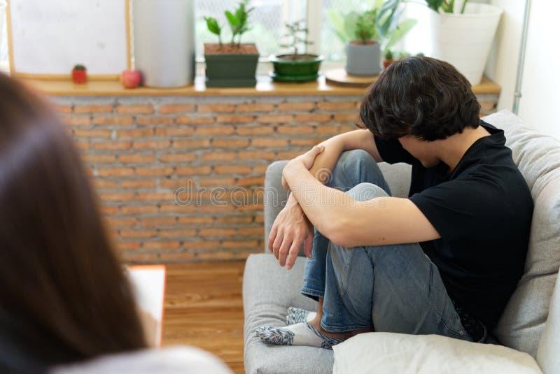 Ung manlig patient som sitter p? soffan med den ledsna framsidan som konsulterar med psykologen royaltyfri fotografi