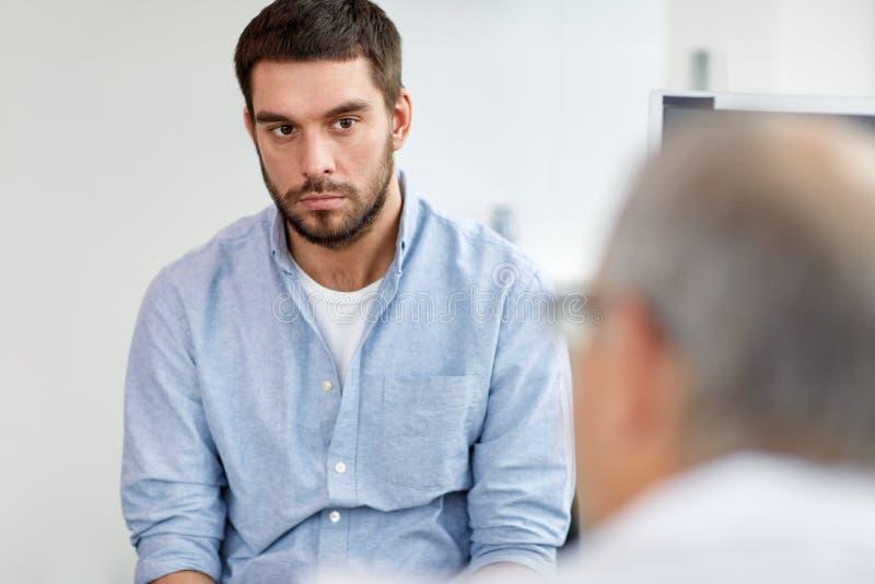 Ung manlig patient som talar till doktorn på sjukhuset royaltyfri bild