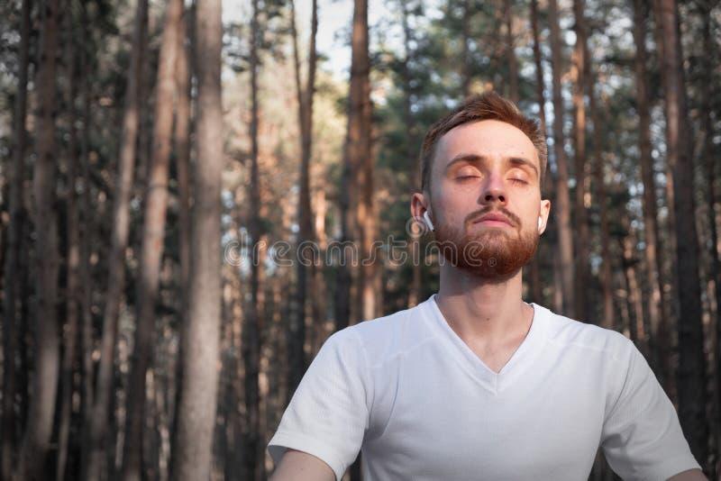 Ung manlig person som mediterar i skogen genom att använda modern teknologi arkivbild
