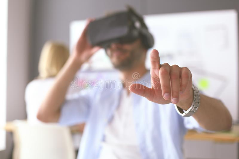 Ung manlig programvaruprogrammerare som i regeringsst?llning testar en ny app med exponeringsglas f?r virtuell verklighet 3d vektor illustrationer