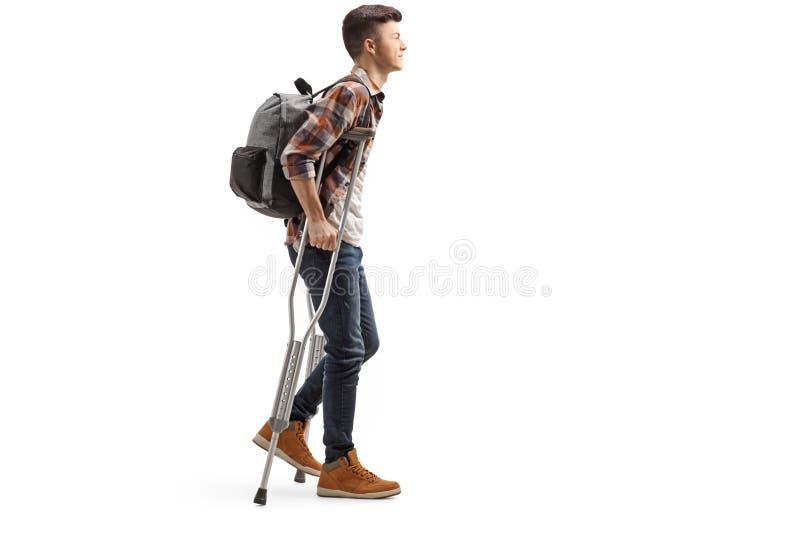 Ung manlig student som går med kryckor royaltyfria foton