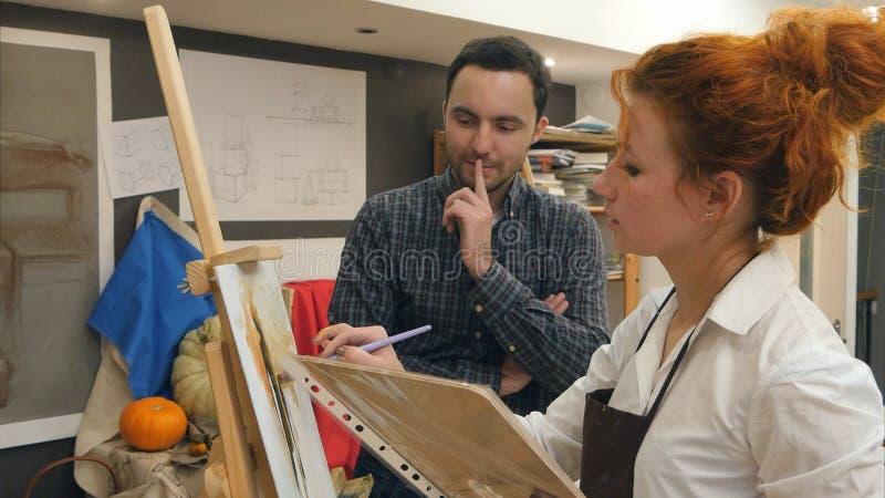 Ung manlig student som håller ögonen på hans läraremålning med olja arkivfoto