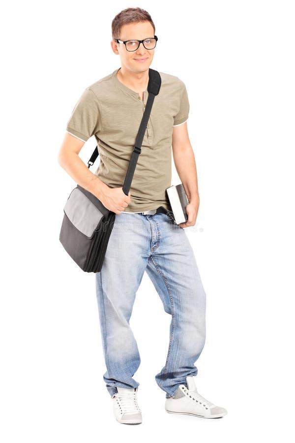 Ung manlig student som rymmer en bok royaltyfri bild