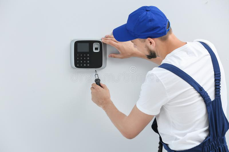Ung manlig tekniker som inomhus installerar larmsystemet royaltyfri bild