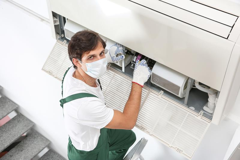 Ung manlig tekniker som reparerar luftkonditioneringsapparaten arkivbilder