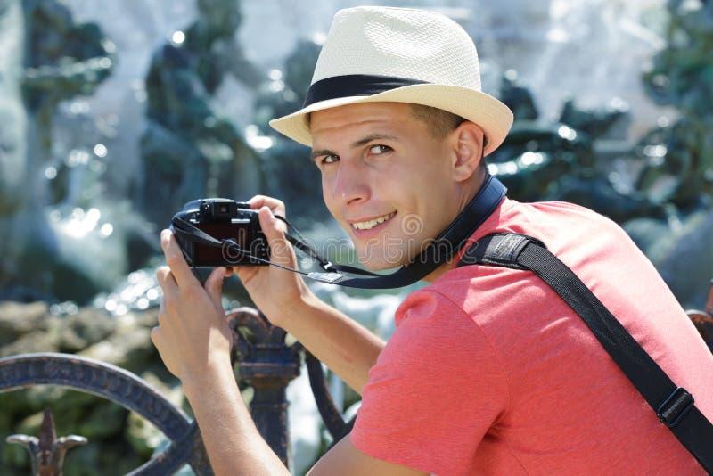Ung manlig turist som tar fotografiet med den digitala kameran fotografering för bildbyråer