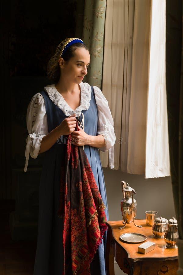 Ung medeltida flicka som väntar på sitt fönster royaltyfri fotografi
