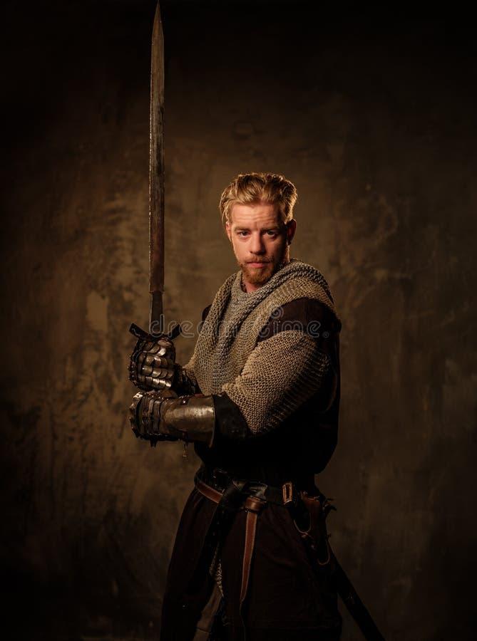 Ung medeltida riddare som poserar på mörk bakgrund royaltyfri bild